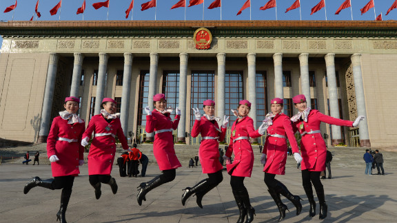 Chinese hostesses jump for the cameras before the Party Congress