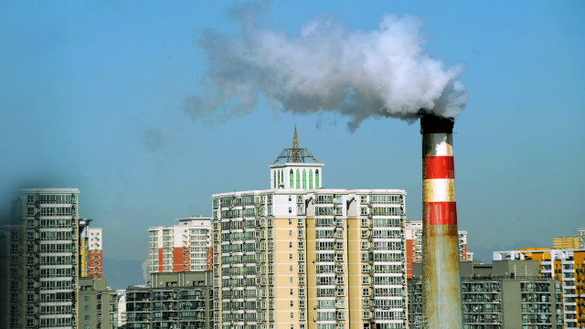 Pollutants billow out of a chimney near residential apartment blocks in Beijing, March 2, 2011.