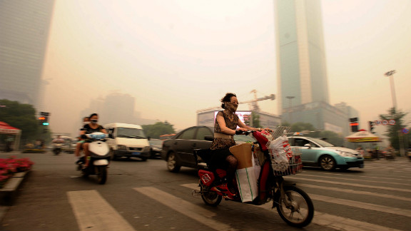 Chinese motorists wear masks as they make their way along a busy intersection in central China's Hubei province in June 2012. A landmark study in 2013 by Chinese and international academics found toxic air slashed an average of five and a half years off life expectancy in northern China.