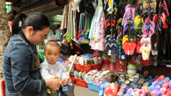 A mother sits with her child outside a shop on a street in Shanghai on May 23, 2012. China