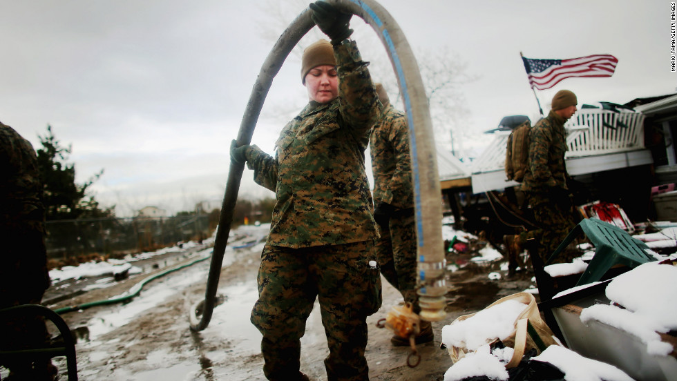Lance Cpl. Trina Azevedo carries a hose to pump out floodwater in Queens.