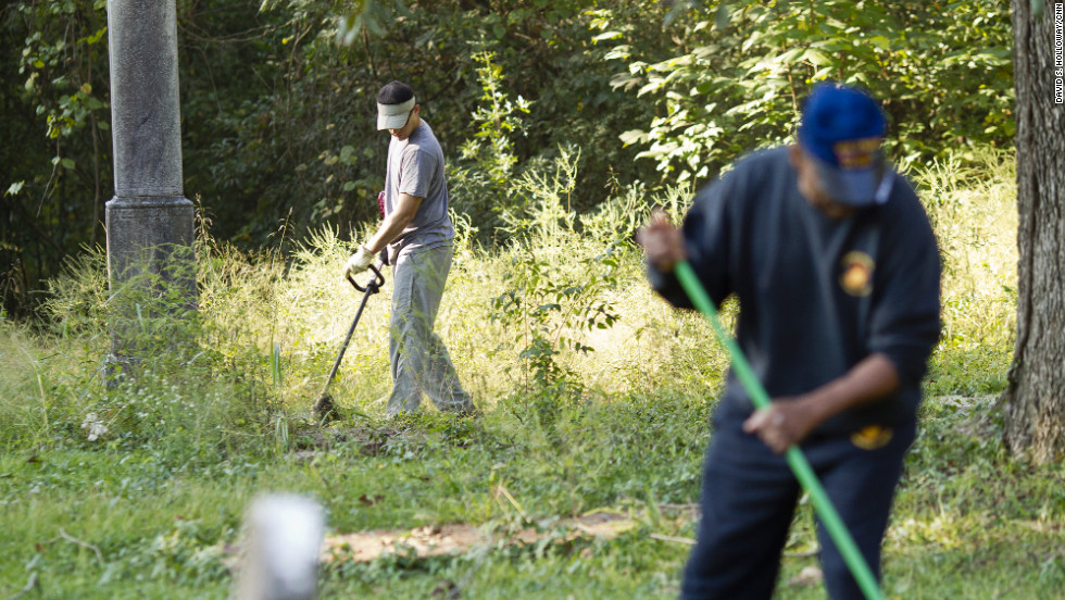 "Volunteers clear the overgrown brush from Linwood Cemetery, which tells the story of Macon's African-American community. Sgt. Rodney Davis' mother insisted on burying him there, instead of Arlington National Cemetery.  Davis' sister, Debra Ray said: ""Mother would say if Rodney wasn't there nobody would care about the cemetery."""