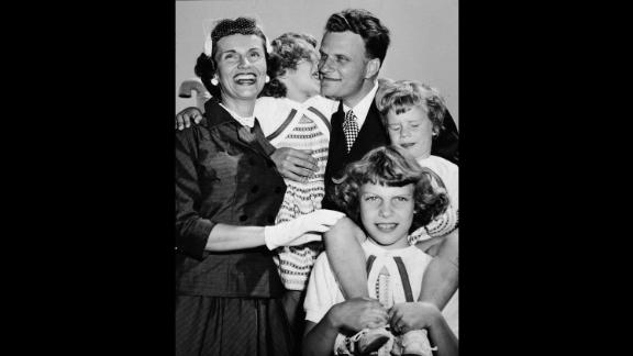 """Graham embraces his family upon his return from his """"Crusade for Christ"""" tour in the 1950s. With him from left are his wife, Ruth, and his daughters Anne, Virginia and Ruth (Bunny)."""