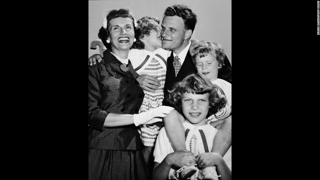 "Graham embraces his family upon his return from his ""Crusade for Christ"" tour in the 1950s. With him from left are his wife, Ruth, and his daughters Anne, Virginia and Ruth (Bunny)."