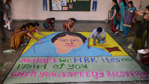 """Indian teachers add finishing touches to a """"Malala Rangoli"""" at a high school in Ahmedabad on Saturday."""