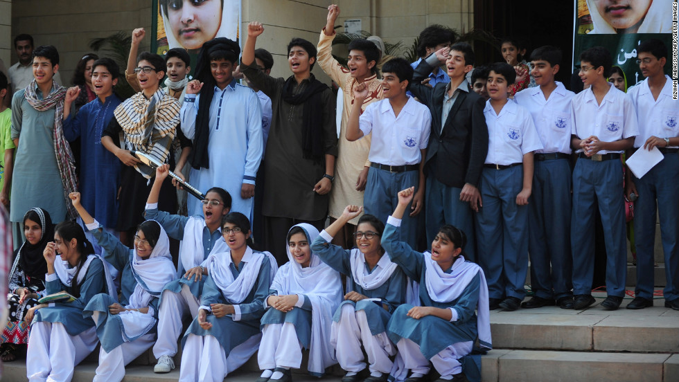 Pakistani students shout slogans near photographs of Malala in Karachi on Saturday.