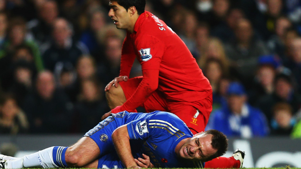 Chelsea captain John Terry is injured after going down in a tackle with Liverpool striker Luis Suarez.
