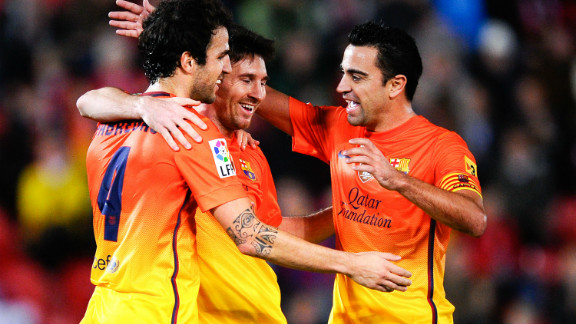 Lionel Messi, center, celebrates with Barcelona teammates Cesc Fabregas, left, and Xavi Hernandez after matching Pele