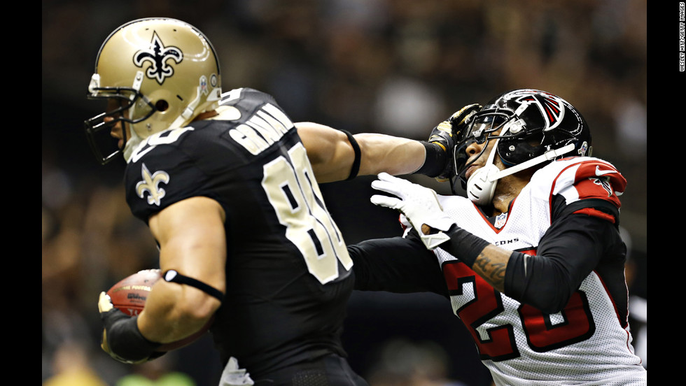 Jimmy Graham of the Saints stiff arms Thomas DeCoud of the Falcons on his way to the end zone for a touchdownon Sunday.