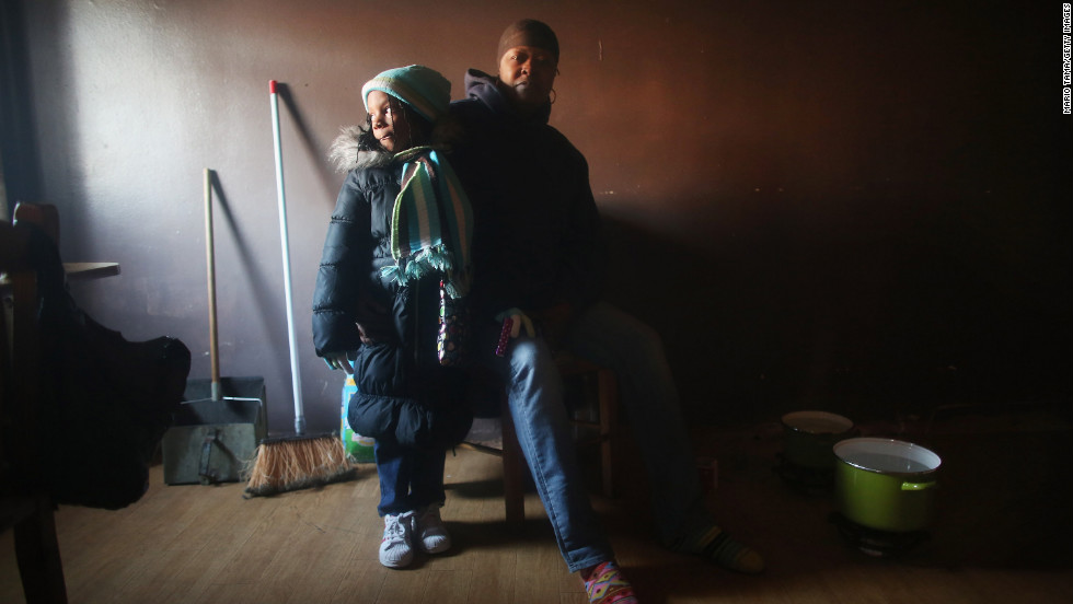 Mac Baker, right, poses with her niece Nytaisha Baker next to pots of water she heats on the floor with small flames for a bit of warmth in Baker's unheated apartment in the Ocean Bay public housing projects in the Far Rockaway neighborhood in Queens on Friday, November 9.