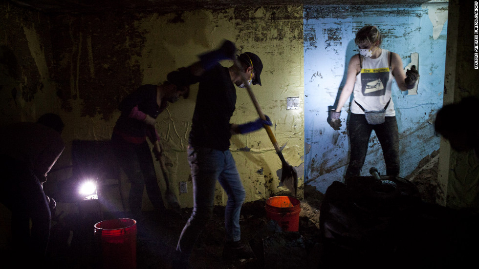 "Volunteers shovel sand and water out of the basement of Monir Islam's home in the Rockaway Park neighborhood of Queens, New York, on Sunday. The Rockaways peninsula in Queens was one of the areas hardest hit by Sandy. <a href=""http://www.cnn.com/2012/11/09/us/gallery/sandy-rockaway/index.html"" target=""_blank"">See photos of Rockaway's continuing struggles</a>."