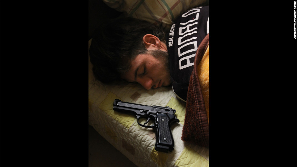 Syrian opposition fighter Bazel Araj, 19, sleeps next to his pistol in Aleppo on November 11, 2012.