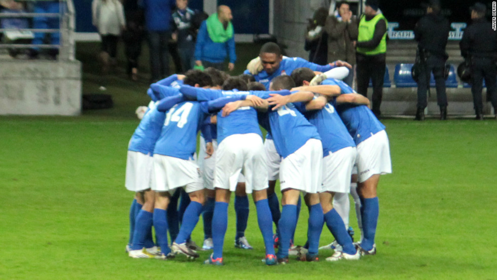 The Real Oviedo players huddle on the pitch before the match.