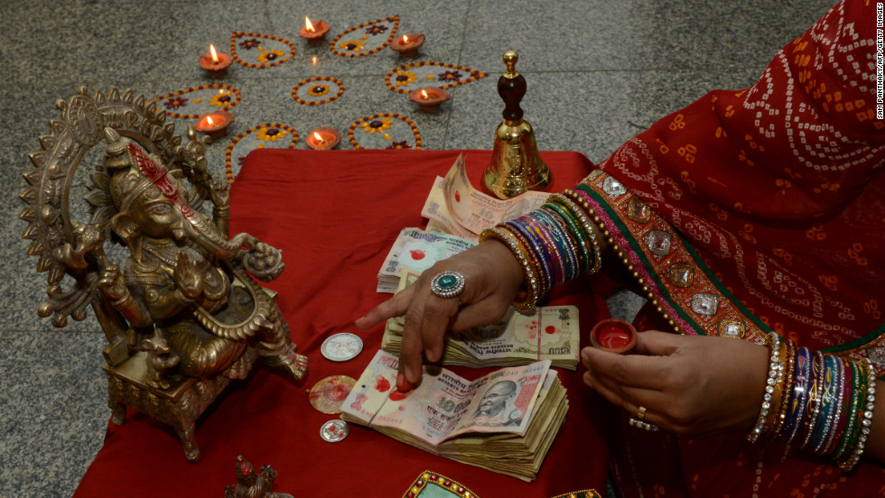 "An Indian observes ""Dhanteras,"" the first day of the five-day Diwali Festival as celebrated in parts of north India, in Ahmedabad on Sunday, November 11. Some Hindus purchase precious metals on Dhanteras for good luck."