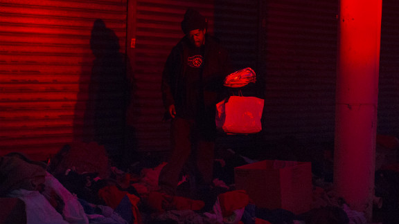 A man looks through donated clothes and supplies at nightfall Monday in Rockaway.
