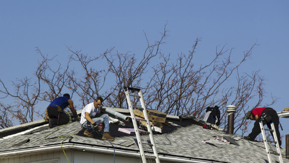Roofers repair damage Monday on a home in the Annadale neighborhood of Staten Island.