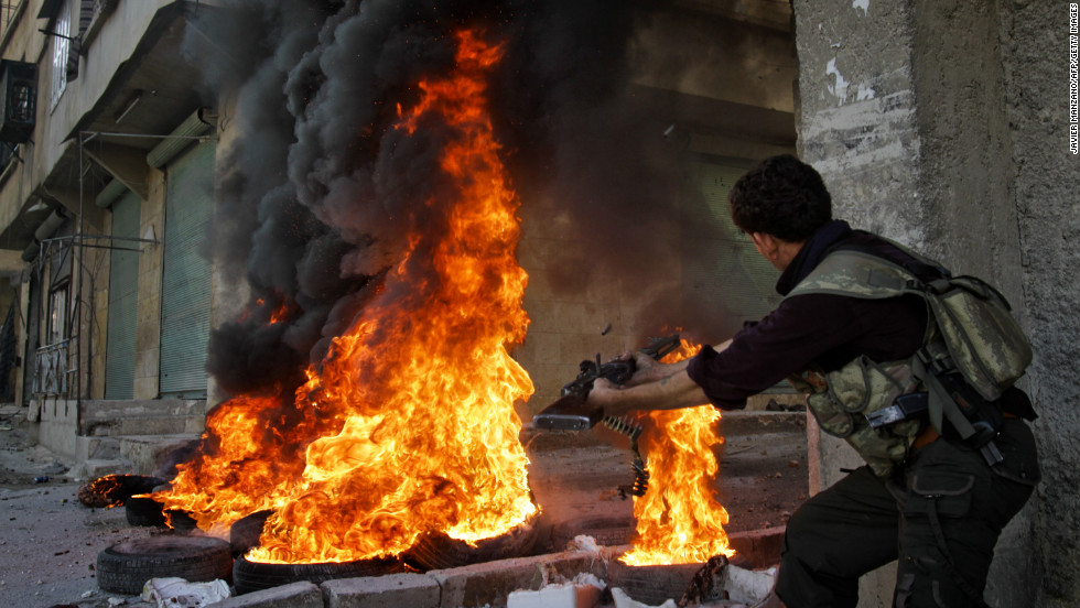 Smoke billows from burning tires as a Syrian rebel fires toward regime forces in Aleppo on Tuesday.