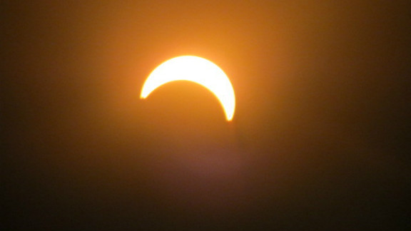 """""""I thought it would be cool to take a few photos because I haven't seen an eclipse in my lifetime, says iReporter Samuel Hill who shot this picture in Wellington, New Zealand. """"Most people were really excited once they got to look through the solar lenses to see the eclipse."""""""