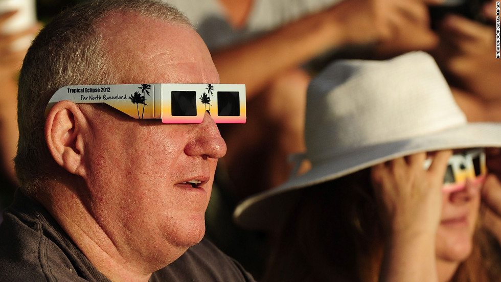 A spectator views the solar eclipse through special eclipse viewing glasses in Palm Cove on Wednesday.