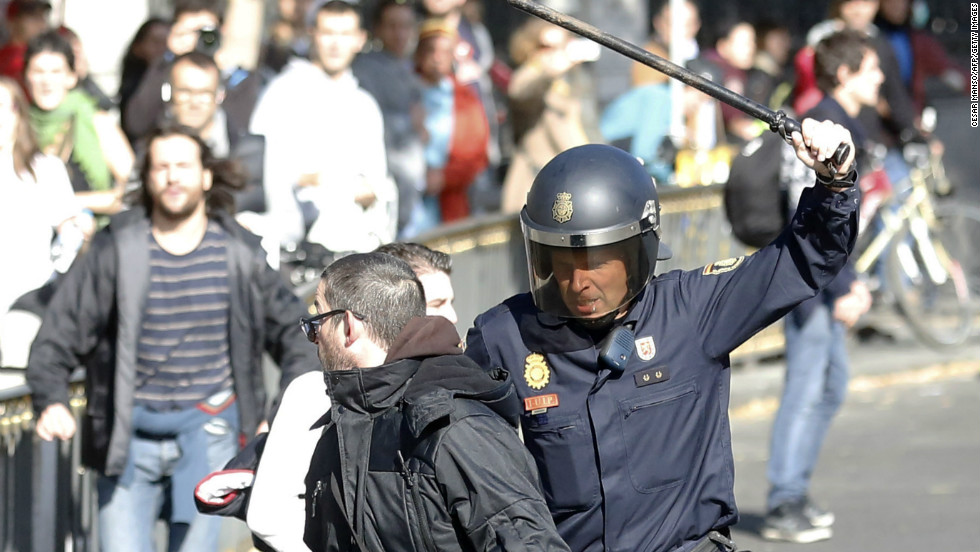 A riot policeman runs after a protester at Cibeles Square in Madrid.
