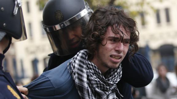 Riot policemen arrest a protester in Valencia on November 14, 2012 during a general strike.