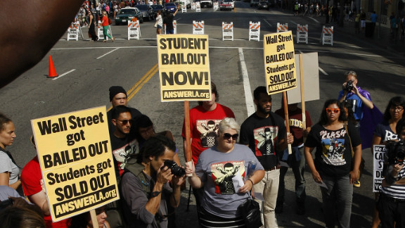 """Demonstrators symbolically """"burn"""" student loan bills in Los Angeles during a protest of rising student loan costs."""