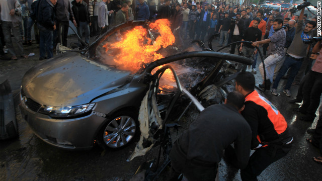 Palestinians extinguish fire from the car of Ahmaed Jaabari, head of the military wing of the Hamas movement, the Ezzedin Qassam Brigades, after it was hit by an Israeli air strike in Gaza City on November 14, 2012. The top Hamas commander Ahmed al-Jaabari was killed in an Israeli air strike , medics