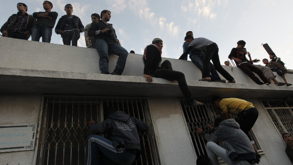 Palestinian youths look inside a building where al-Jaabari