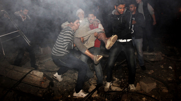 Palestinian youths evacuate an elderly man following an Israeli airstrike.