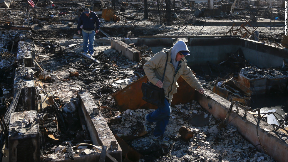 Insurance claims adjusters walk past burned-out houses Wednesday in the Breezy Point section of Queens, New York. A fire that broke out in the neighborhood during the storm destroyed more than 100 homes.