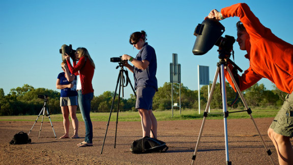 """David Freeman of Longreach in outback Queensland sent in this image of photographers prepping for the big moment. """"Even if we didn't get totality the light was really interesting,"""" he says. """"Coming so close after sunrise we had the typical outback orange and red sunrise and then went into an almost surreal subdued light. Not the same colors as a normal sunrise but definitely not normal daylight either."""""""
