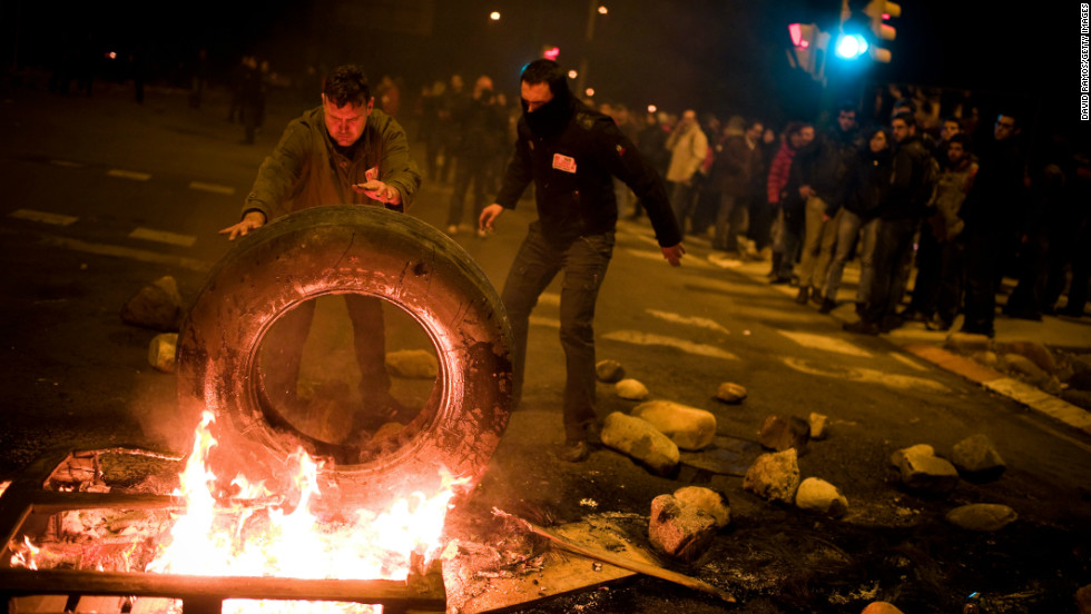 In Barcelona, demonstrators set up a barricade of burning tires.