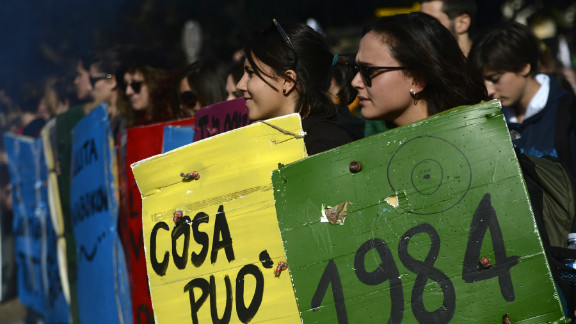 Students hold placards with titles of classic books during a protest on a day of mobilization against austerity measures by workers in southern Europe on November 14, 2012 in Rome.