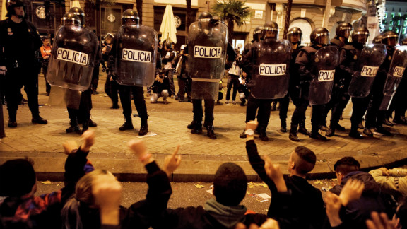 Protesters sit down in front of a line of police.