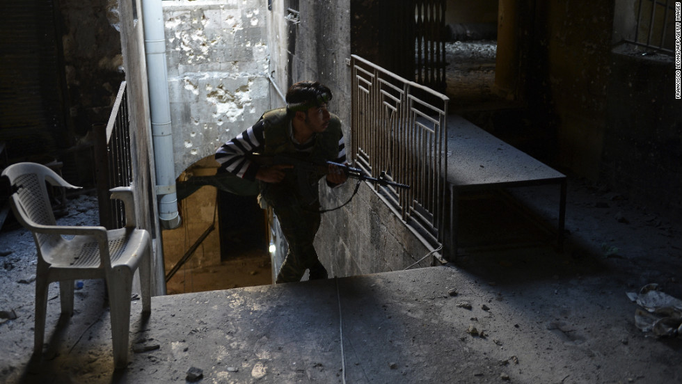 A Syrian rebel takes cover during fighting against Syrian government forces in Aleppo on November 15, 2012.