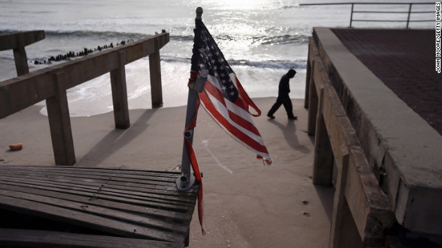 A tattered flag flies over the storm-damaged boardwalk in Rockaway, Queens, on Thursday.