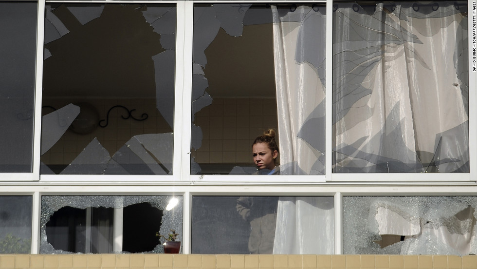 An Israeli woman looks out from an apartment building in Ashdod, Israel, damaged by a rocket fired by Palestinian militants on Friday, November 16.
