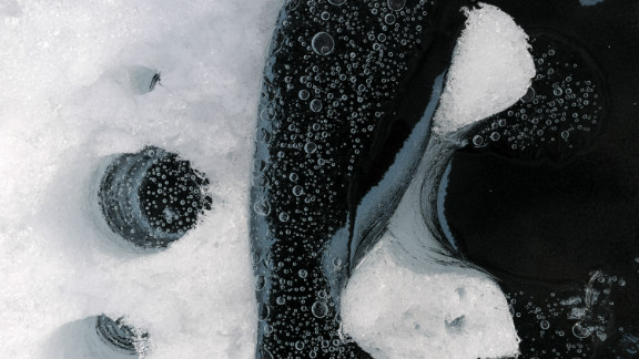 """Greenland Ice Sheet, Greenland, July 2008, Silt and soot blown from afar turn into black """"cryoconite,"""" absorb solar heat and melt down into ice. Courtesy of James Balog"""
