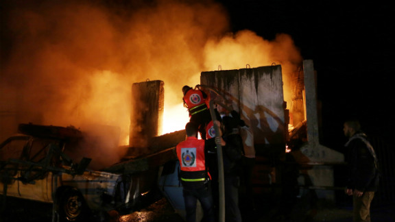 Palestinians extinguish a fire after Israeli air strikes targeted an electricity generator that fed the house of Hamas