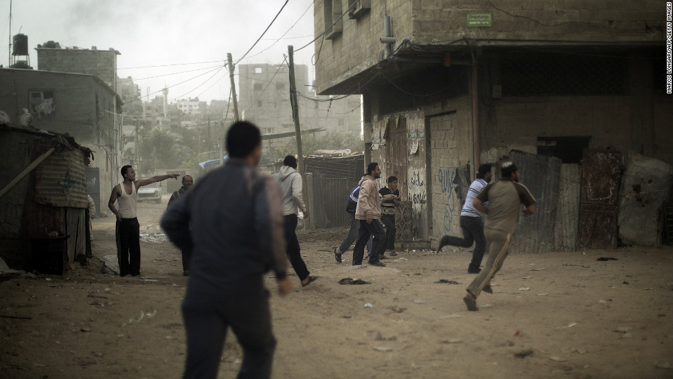 Palestinians run for cover after an Israeli airstrike hits Gaza City on Friday, November 16.