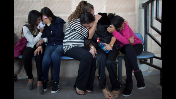 Relatives take cover from a rocket attack during the funeral for Itzik Amsalem in Kiryat Malachi, Israel, on Friday, November 16.