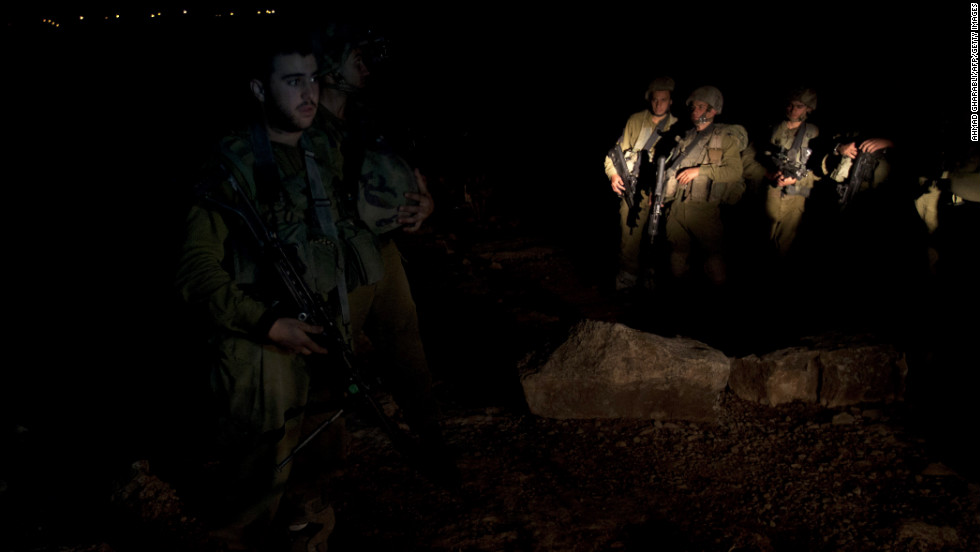 Israeli soldiers stand guard while explosives experts examine the site where a rocket fired from the Gaza Strip landed near the Jewish settlement of Gush Etzion in the village of Kisan, south of Bethlehem on Friday, November 16.