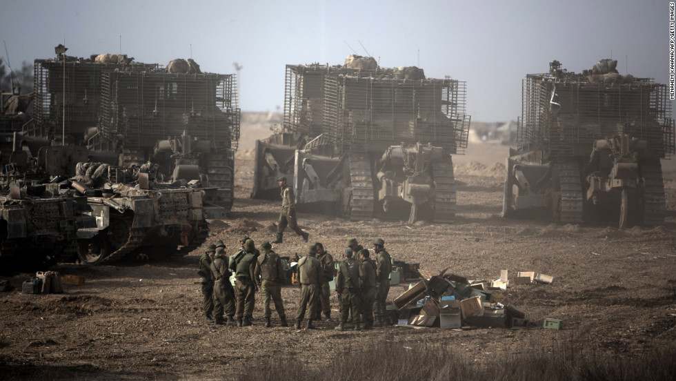 Israeli soldiers gather next to their armored bulldozers stationed on Israel's border with Gaza on Saturday, November 17.