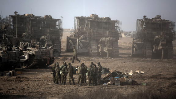 Israeli soldiers gather next to their armored bulldozers stationed on Israel