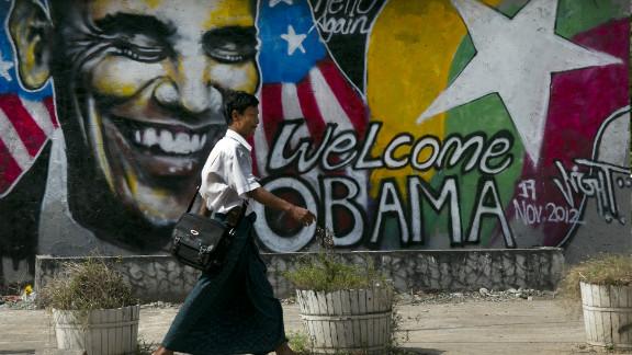 A Burmese man walks by graffiti depicting the U.S. president on Saturday in Yangon.