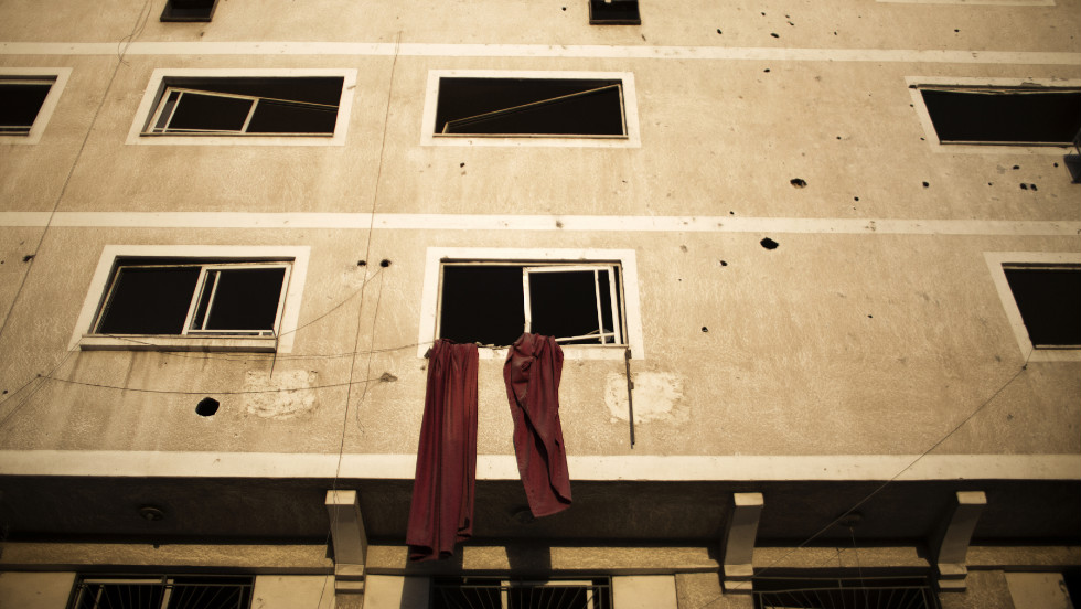 Cloth hangs from a window of a building damaged during Israeli air strikes on Gaza City on Sunday, November 18.