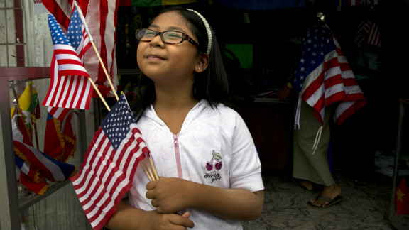 A girl holds American flags that she just purchased at a flag shop as Yangon, Myanmar, prepares for Obama