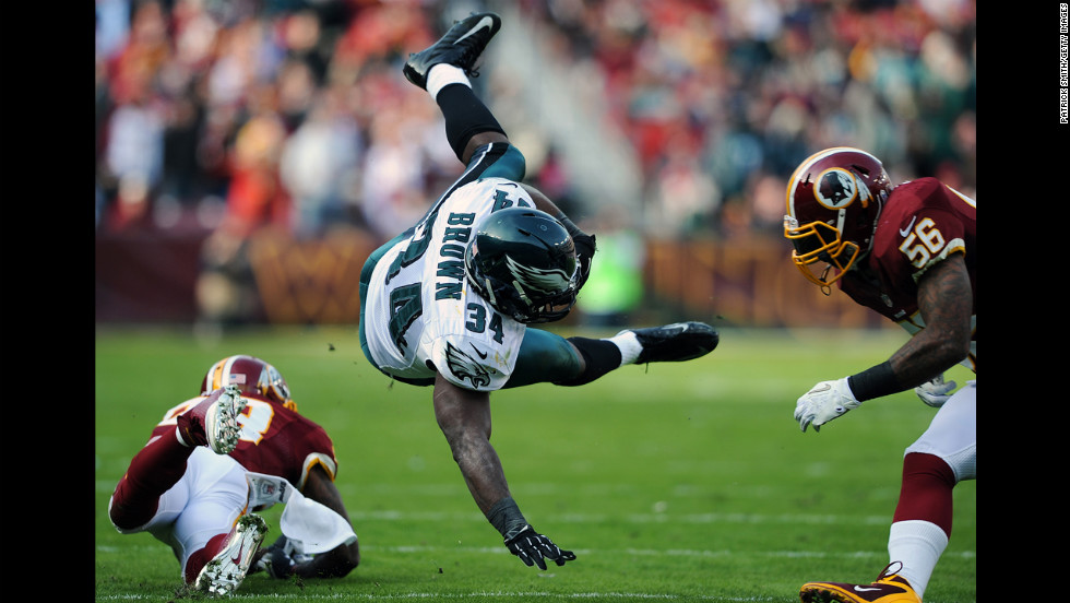 Running back Bryce Brown of the Eagles is upended by Redskins defenders in the second quarter on Sunday.
