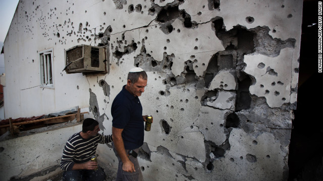 Israelis inspect the damage caused to a house by a rocket launched by Palestinian militants from the Gaza Strip in the southern Israeli town of Ofakim on November 18, 2012. Since the start of its Operation Pillar of Defence, launched after the killing of top Hamas military commander Ahmed Jaabari in an air strike, the Israeli army says Palestinian militants have fired more than 800 rockets over the border. AFP PHOTO/MENAHEM KAHANA (Photo credit should read MENAHEM KAHANA/AFP/Getty Images)