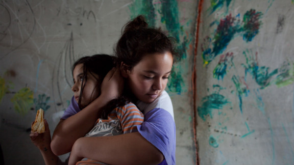 An Israeli girl holds her sister as they take cover in a large concrete pipe used as a bomb shelter during a rocket attack from the Gaza Strip on Monday in Nitzan, Israel.